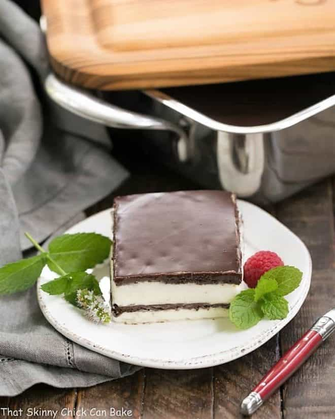 No Bake Chocolate Lasagna slice on a white plate with a mint and a fresh raspberry