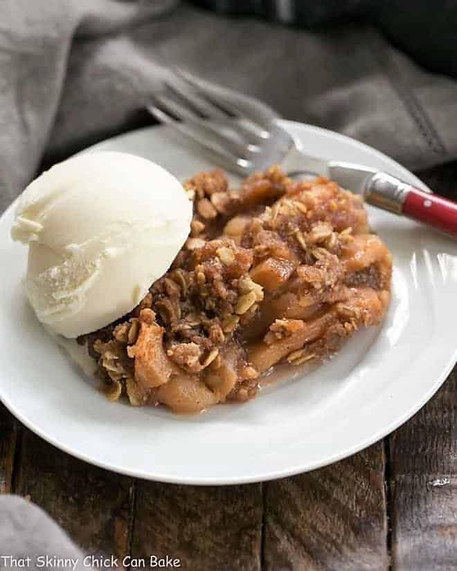Easy Slow Cooker Apple Crisp with Oatmeal on a white dessert plate with a scoop of ice cream