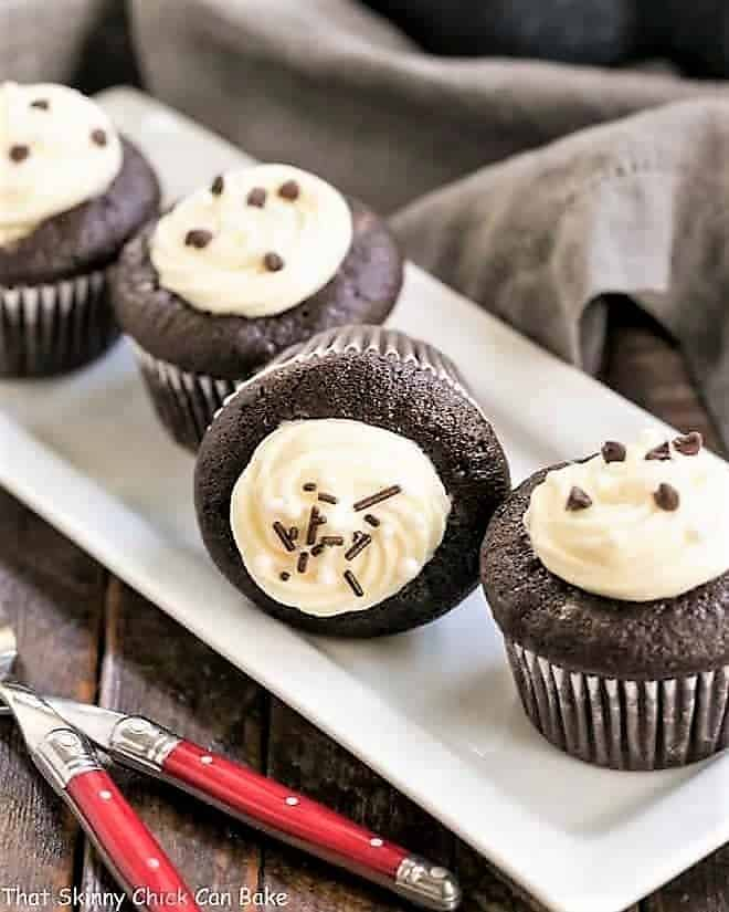 Frosted Black Bottom Cupcakes on a ceramic tray with red handled forks