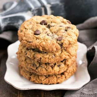 Loaded Cowboy Cookies stacked on a square white plate