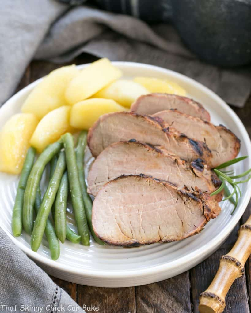 Sliced Maple Grilled Pork Tenderloin with apples and green beans on a white dinner plate