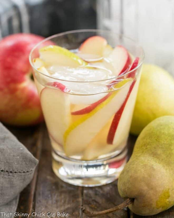 Apple Cider Sangria in a highball glass with ice, apple and pear slices