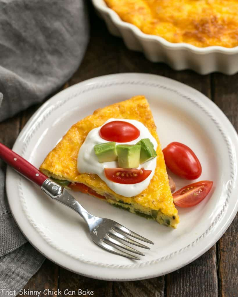 Baked Denver Omelet slice on a white plate with a red handled fork