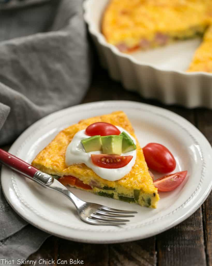 Baked Denver Omelet slice on a white plate with the casserole dish in the background