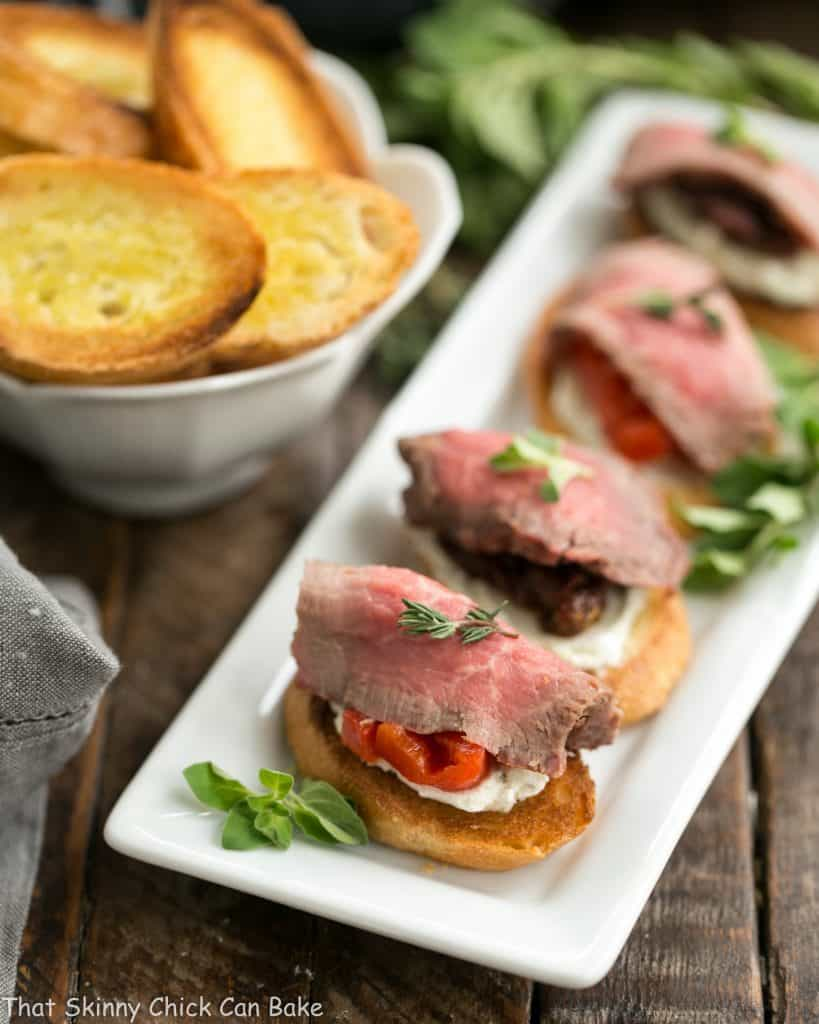 Beef Crostini with Blue Cheese Spread | Baguette toasts smeared with a blue cheese spread and topped with peppers or tomatoes and rare grilled beef!