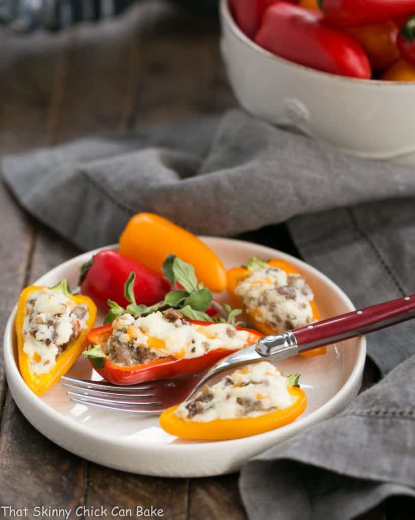 Cream Cheese Stuffed Mini Peppers with Sausage on a small white plate with a red handled fork