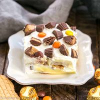 Peanut Butter Cookie Lasagna | An incredible no-bake dessert layered with pb sandwich cookies, vanilla pudding, whipped cream, pb cups and a drizzle of melted peanut butter!!