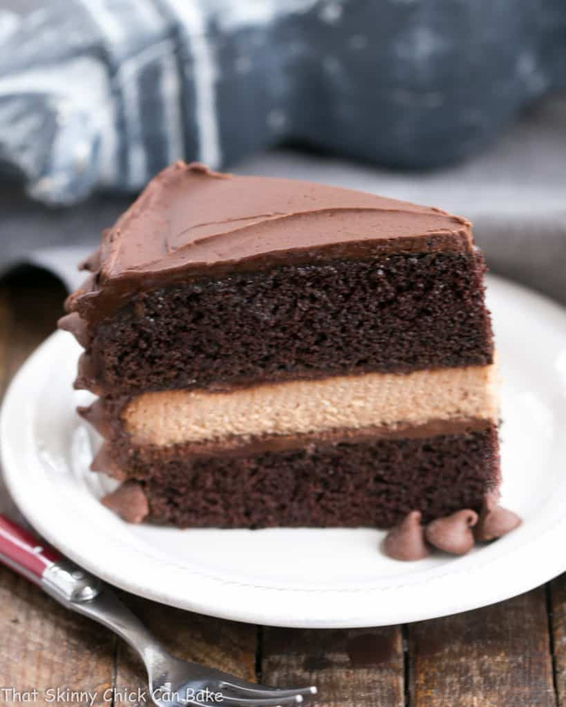 a slice of rich chocolate layer cake with a filing of milk chocolate cheesecake