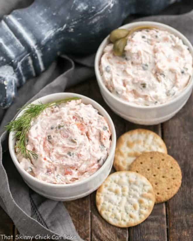 2 bowls of creamy smoked salmon dip with crackers on the side