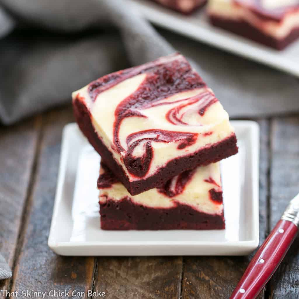 red velvet cheesecake brownies on a square white dessert plate
