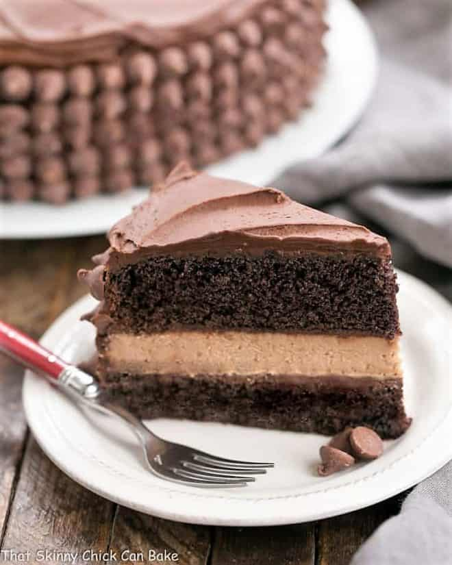 a slice of chocolate layer cake with chocolate cheesecake between the layers