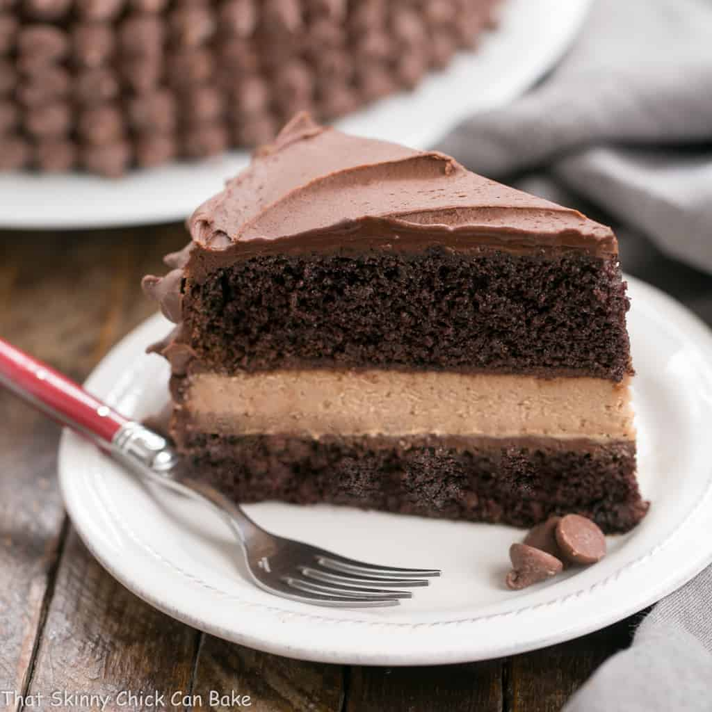 a slice of Candy Bar Cheesecake - chocolate layer cake with a chocolate cheesecake filling