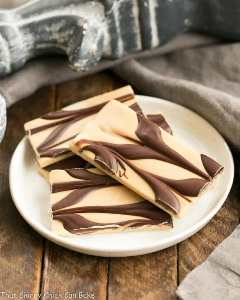 Four pieces of Peanut Butter Chocolate Tiger Bark on a small, round white plate