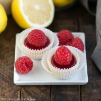 Raspberry Topped Mini Cheesecakes | Creamy mini cheesecakes topped with raspberry sauce and a plump ripe raspberry!