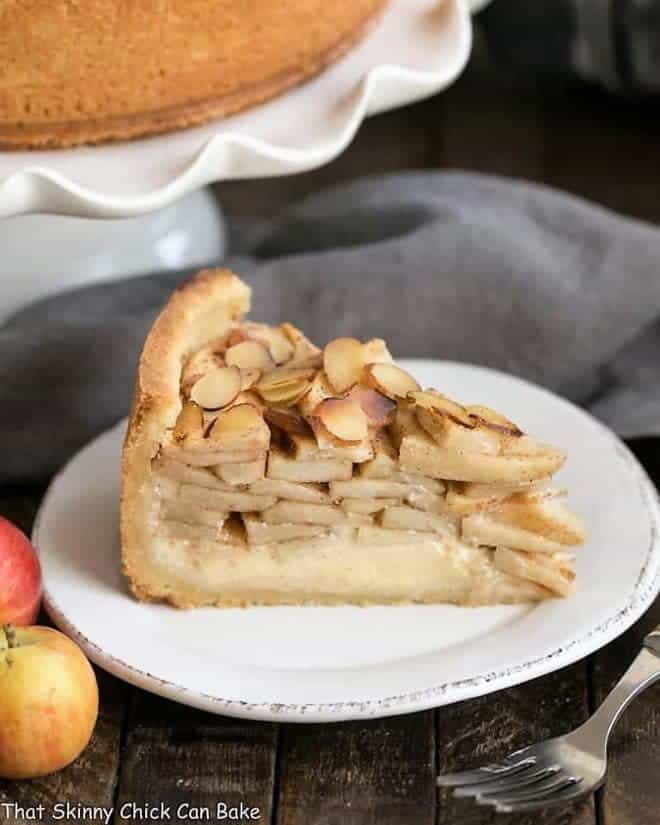Cream Cheese Apple Torte on a white dessert plate with cake stand, apples and fork
