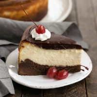 Hot Fudge Brownie Cheesecake featured image on a white plate with cherries