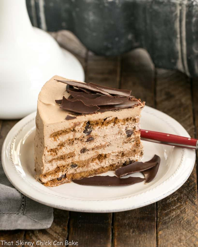 Mocha Chocolate Chip Cookie Icebox Cake slice on a white plate with chocolate shards