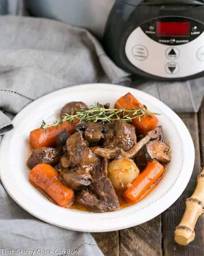 Slow cooker beef stew with mushrooms in a white soup bowl