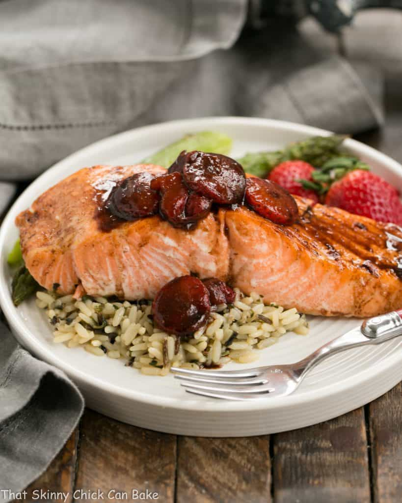 Strawberry Glazed Salmon on a white dinner plate with rice and fresh strawberries