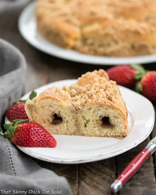 Slice of Copycat Butter Streusel Copycat Recipe on a white plate with strawberries