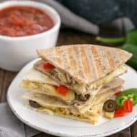 Stack of chicken quesadillas on round white plate