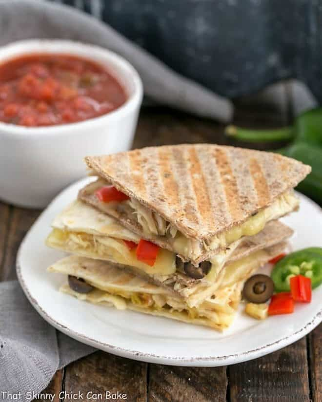 Cheesy Chipotle Chicken Quesadillas stacked on a round white plate