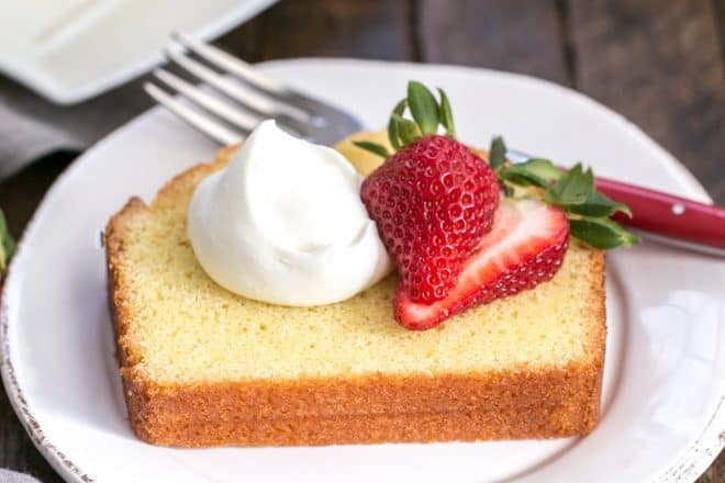 Glazed Lemon Pound Cake - served with whipped cream and berries for a delightful dessert