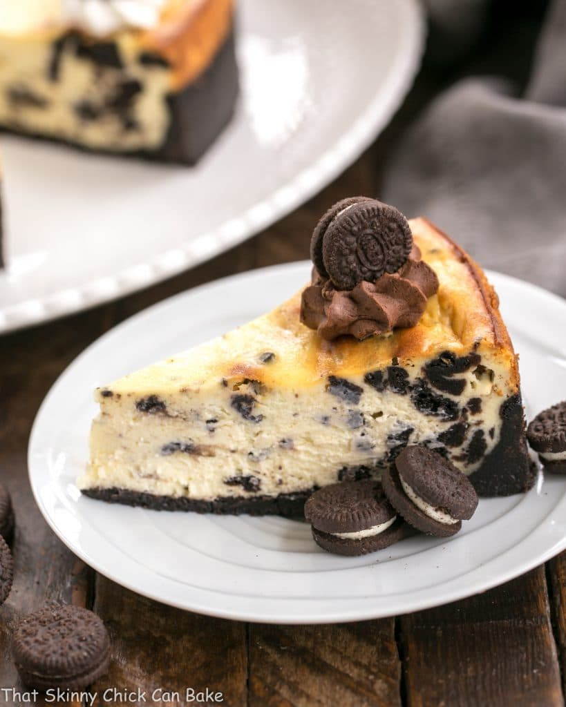 Slice of Oreo Cheesecake with Oreo Cookie Crust on a white plate