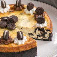 Oreo Cheesecake with Oreo Cookie Crust with slice gone on white serving plate