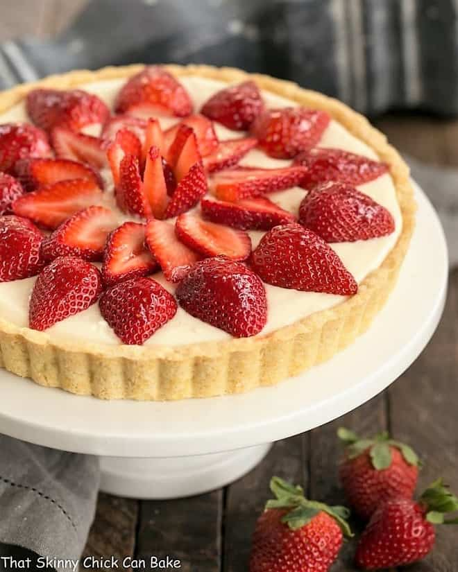 Strawberry Lemon Tart on a cake stand with fresh strawberries