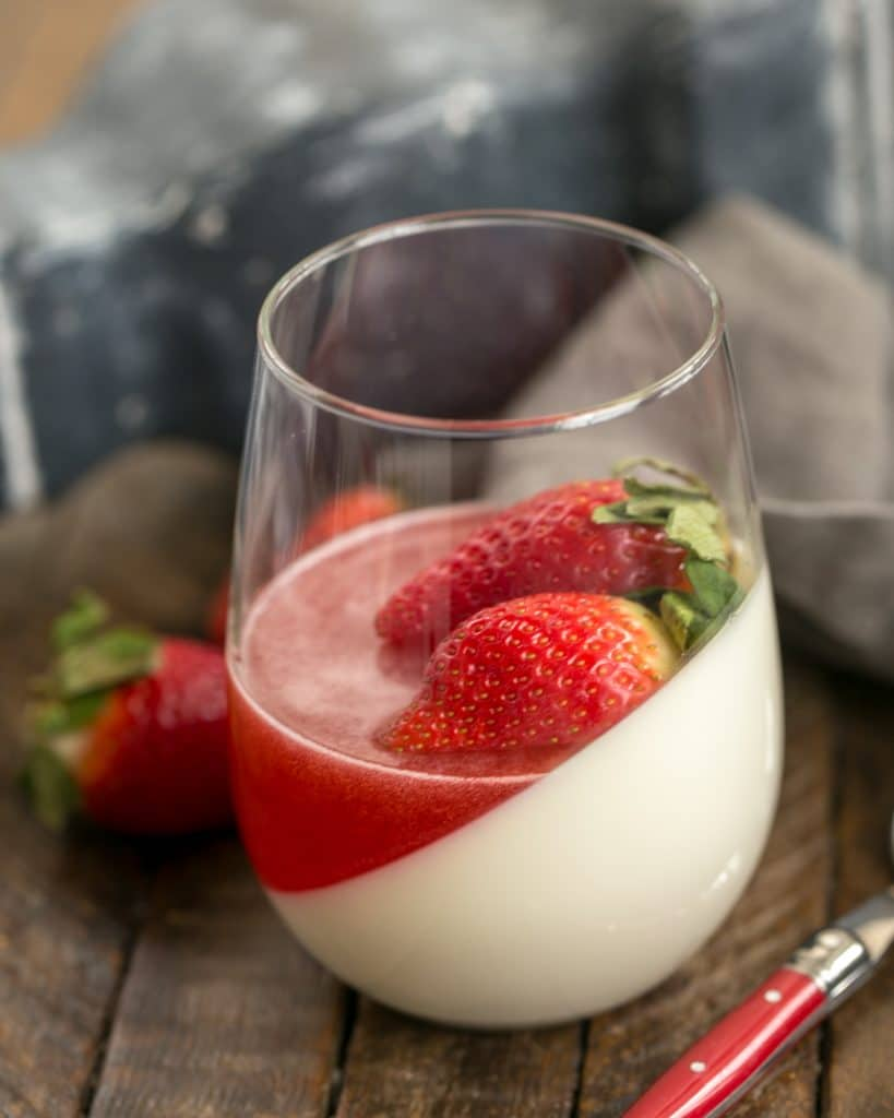 Vanilla Panna Cotta with Strawberry Gelée in a glass topped with fresh strawberries