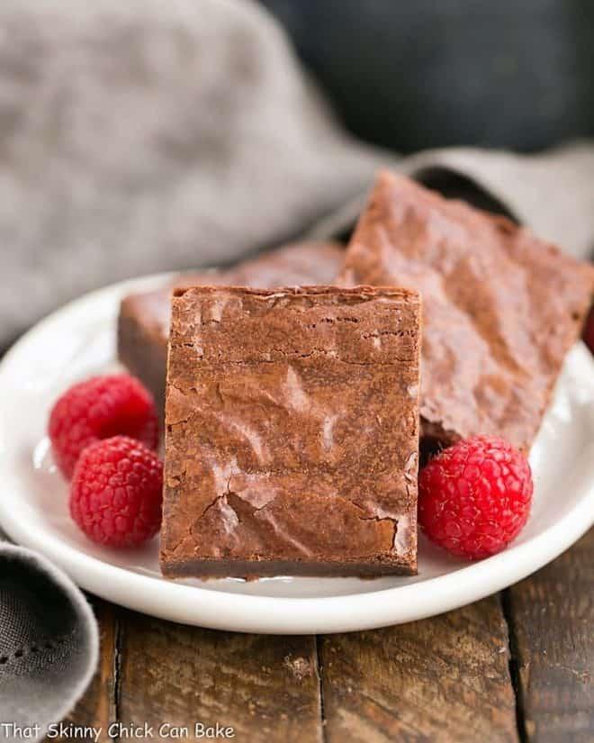 Best Fudgy Brownies on a round dessert plate with raspberries to garnish