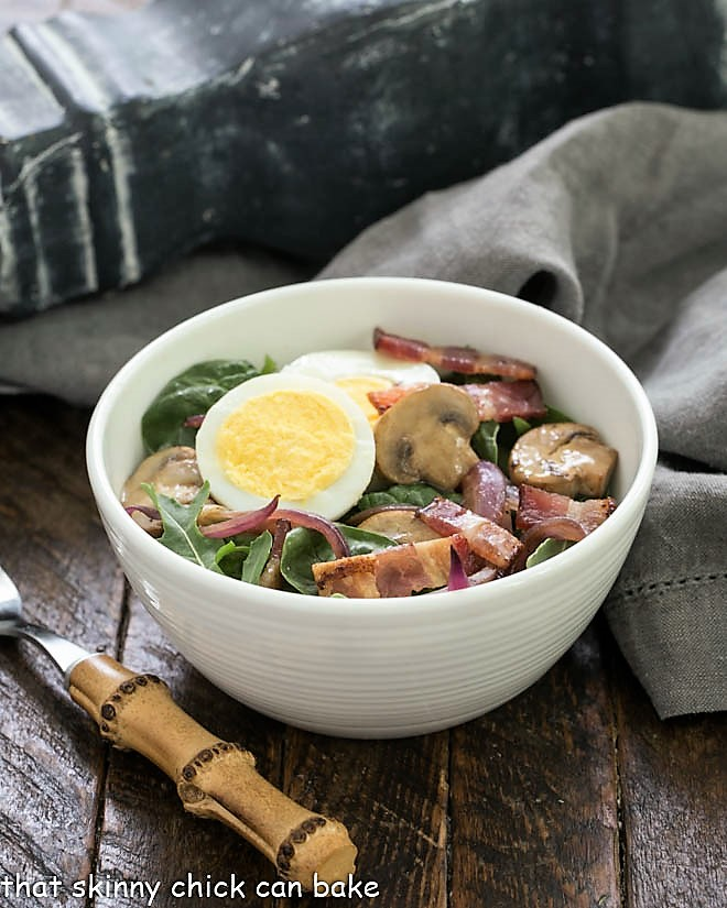 Salad bowl with a spinach bacon salad with a bamboo handle fork