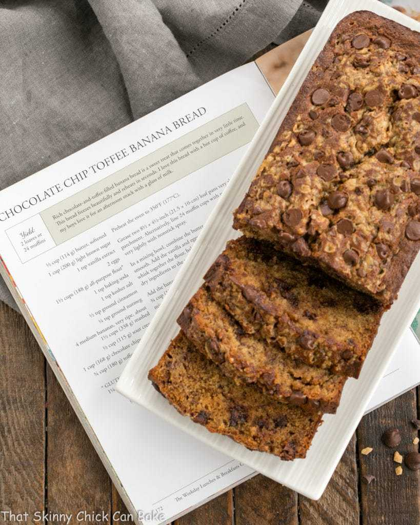 Chocolate Chip Toffee Banana Bread sliced, on a white platter, resting on a cookbook