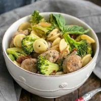 Sun-dried Tomato and Sausage Pasta with Broccoli in a white ceramic bowl