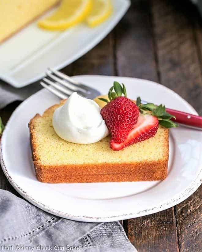 Glazed Lemon Pound Cake slice plated with berries and cream