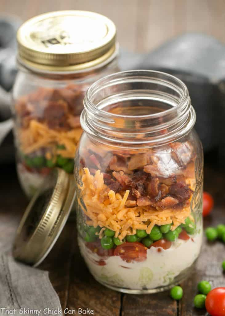 Two Make Ahead 7-Layer Salads in a Jar, one with the lid off