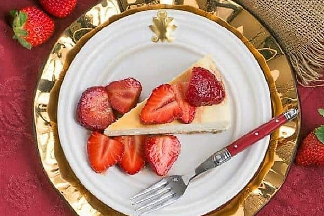Mascarpone Cheesecake with Balsamic Strawberries overhead view on a white plate over a gold charger plate