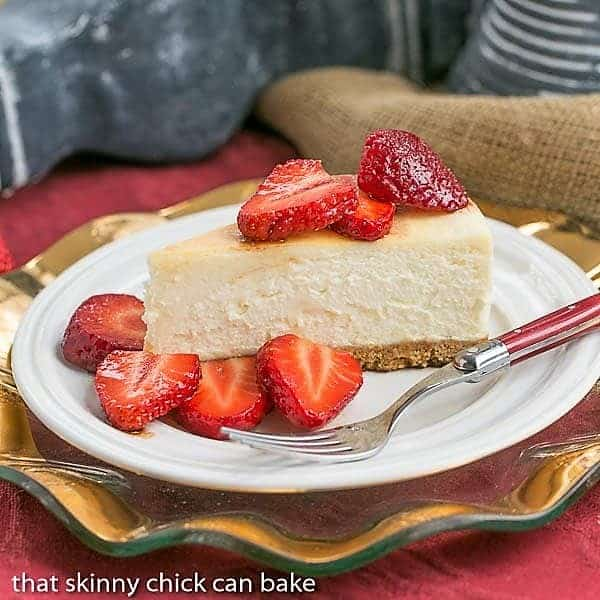 Mascarpone Cheesecake with Balsamic Strawberries on a white dessert plate with a red handled fork