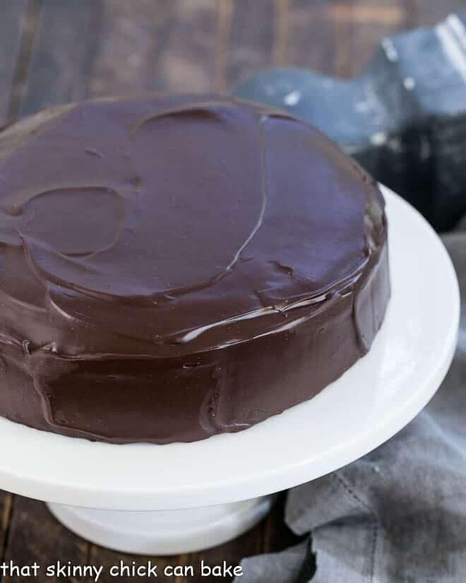 One Layer Fudge Cake on a white ceramic cake stand