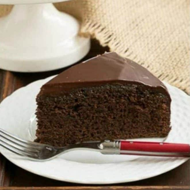 Slice of One Layer Fudge Cake on a white plate with a red handled fork