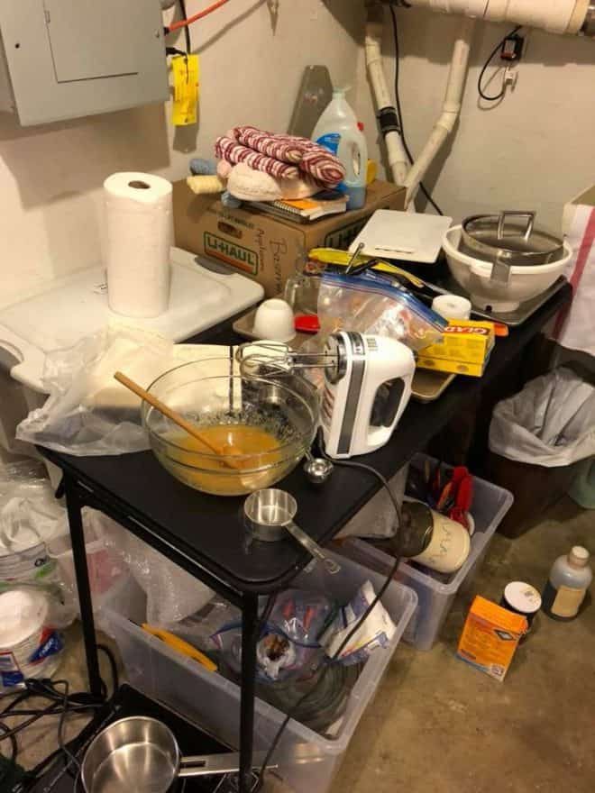 Makeshift basement kitchen with a card table, mixer, buckets of kitchen supplies