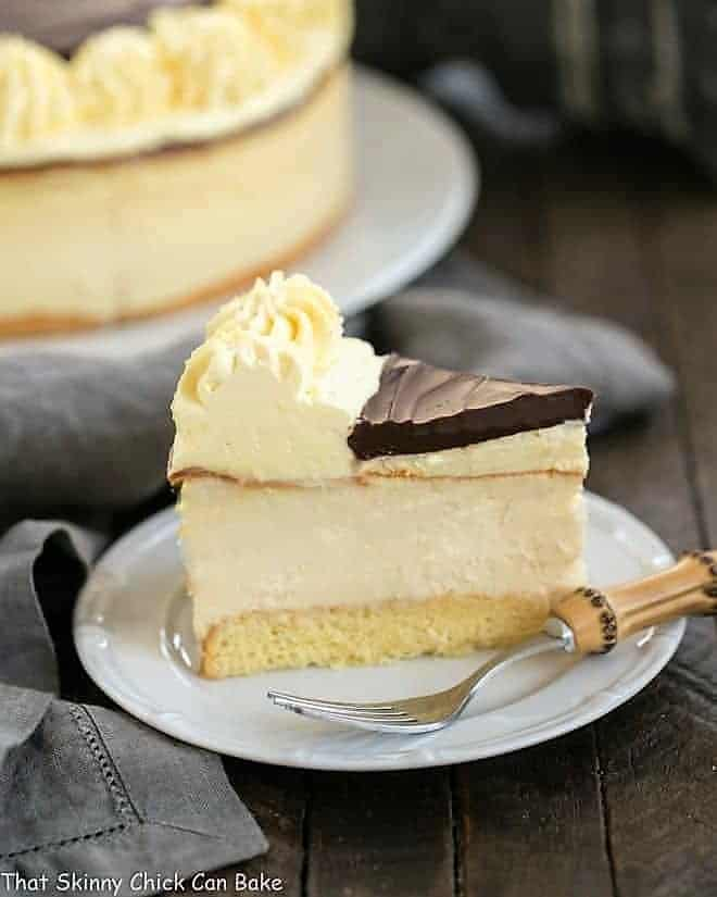 Slice of Boston Cream Pie Cheesecake on a white plate with a bamboo fork