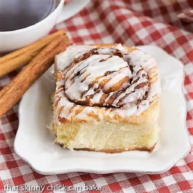 The Best Cinnamon Rolls on a square white plate with cinnamon sticks on a red and white checked napkin.
