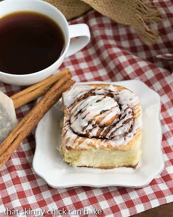 Overhead view of one of The Best Cinnamon Rolls on a white plate with a cup of tea
