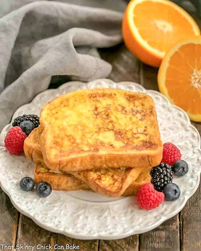 Grand Marnier French Toast stacked on a decorative plate with fresh berries