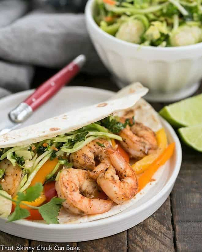 Spicy Shrimp Fajitas on a white plate with a red handled fork