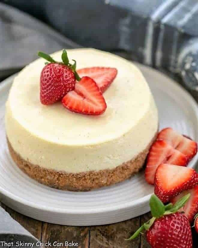 Vanilla Bean Instant Pot Cheesecake  on a white serving plate garnished with strawberries
