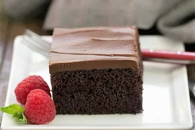 A slice of Black Magic Snack Cake on a white square plate with a raspberry garnish