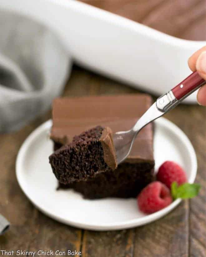 Black Magic Snack Cake slice on a round plate with a red fork with small piece of cake in the foreground